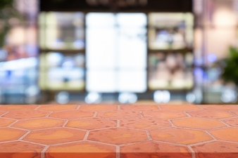 Perspective empty mon brick flooring (clay brick) over blurred shopping mall background.