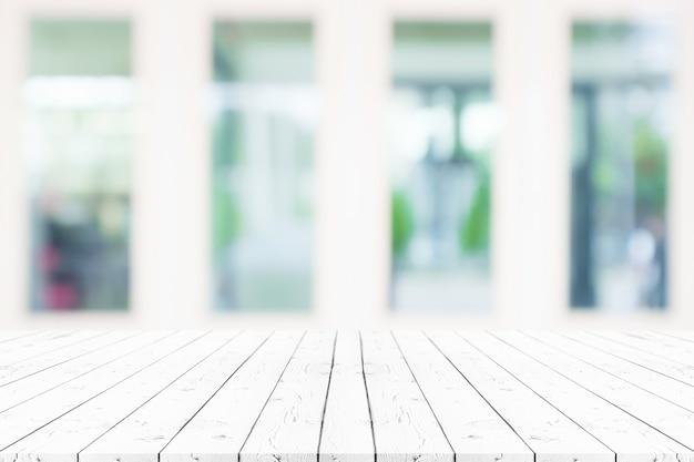 ぼやけた背景の上にある視点の空の白い木製のテーブルは、モンタージュ製品の表示やデザインレイアウトのモックアップに使用できます。