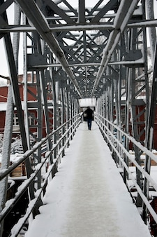 Perspective view of an metal footbridge crossing a railway line.