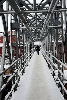線路を横切る金属製歩道橋の斜視図。