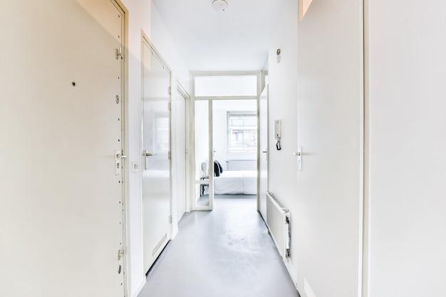 흰 벽과 현대적인 미니멀 스타일 아파트의 침실로 이어지는 열린 문이있는 빈 좁은 복도의 투시도