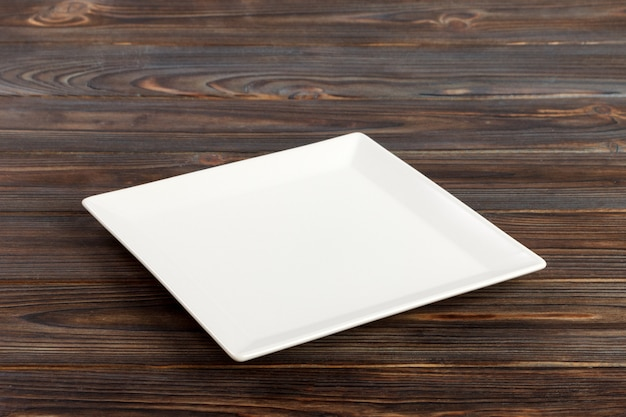 Perspective view a square plate on the white wooden table