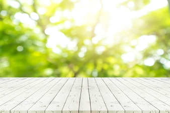 Perspective white wooden table on top over blur natural background