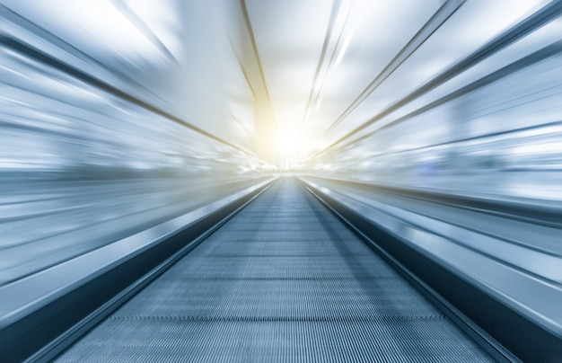 Perspective wide angle black and white view of modern light blue illuminated and spacious high-speed moving escalator with fast blurred trail of handrail in vanishing traffic motion
