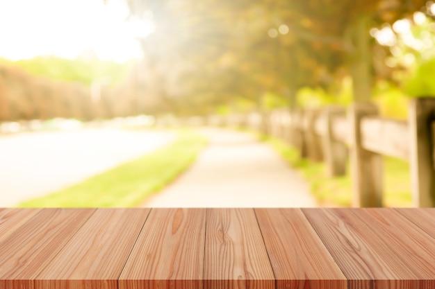 自然な背景をぼかす上にあるパースペクティブ木製テーブルは、モンタージュ製品の表示やデザインレイアウトのモックアップとして使用できます。