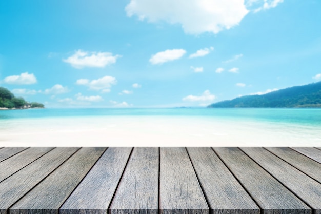 Perspective wooden table on top over blur sea in sunny day background.