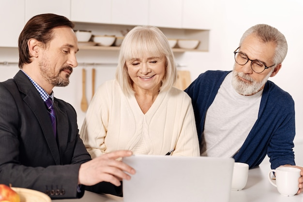 有益な選択を説得する。家の計画を提示し、ラップトップを使用しながら、顧客の老夫婦と会う楽観的な自信を持って熟練した不動産エージェント