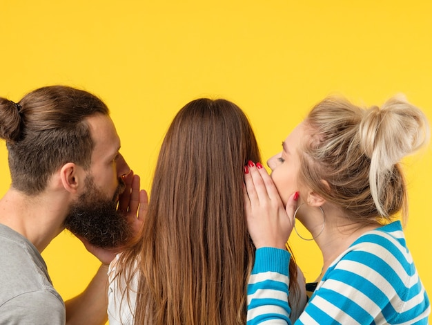 설득 개념. 남자와 여자의 귀에 속삭이는. 노란색 벽에 공간을 복사합니다.