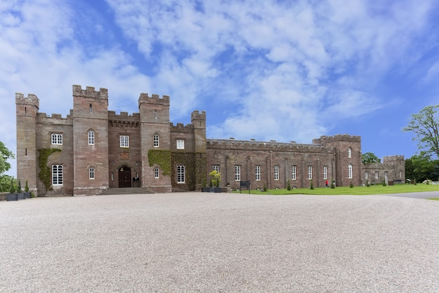 Perth, scotland - may 25 , 2019 : scone palace built of red sandstone with a castellated roof, it is one of the finest examples of late georgian gothic style in scotland