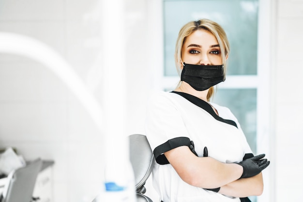 Pertrait фото женщина-врач в черной маске и черные перчатки.