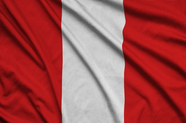 Peru flag is depicted on a sports cloth fabric with many folds.