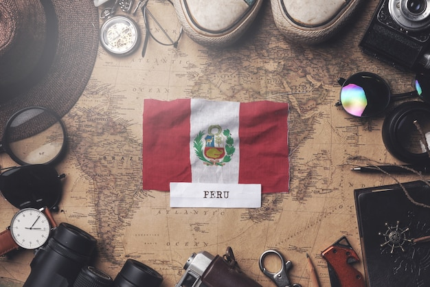 Peru flag between traveler's accessories on old vintage map. overhead shot