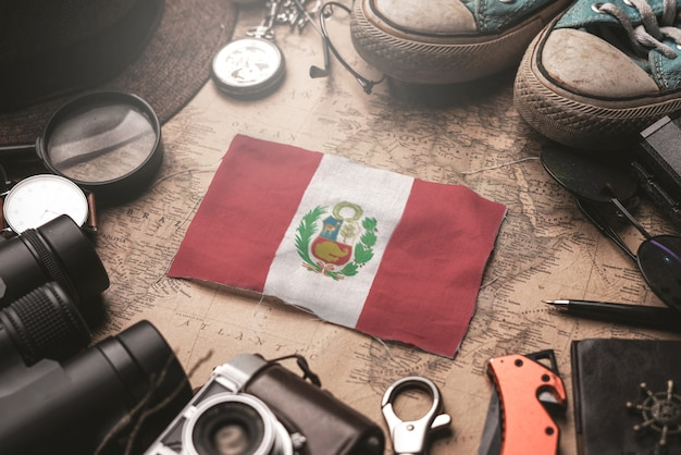 Peru flag between traveler's accessories on old vintage map. tourist destination concept.