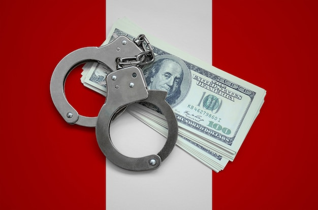 Peru flag  with handcuffs and a bundle of dollars. currency corruption in the country. financial crimes
