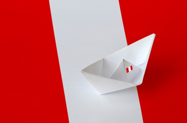 Peru flag with paper origami ship