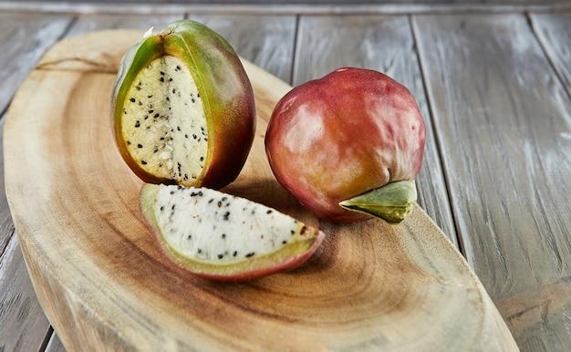 Перуанский яблочный кактус целиком и отрезанный на деревянной подставке на серой доске. научное название cereus repandus