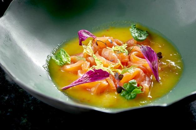 페루 요리 요리-뜨거운 고추, 양파, 노란색 소스를 곁들인 연어 세비체는 대리석 테이블에 파란색 접시에 담겨 있습니다. 레스토랑 해산물.