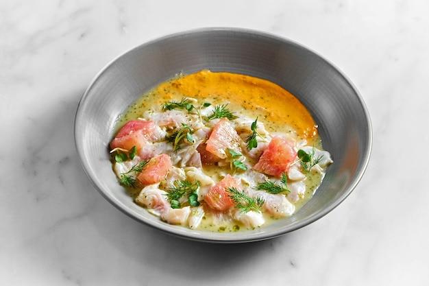 Блюдо перуанской кухни - севиче из морского окуня с грейпфрутом и желтым соусом, подается в серой тарелке на мраморной поверхности. ресторан морепродуктов