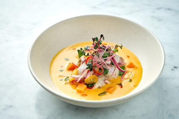 페루 요리 요리-뜨거운 고추, 양파 및 노란색 소스를 곁들인 농어 세비체는 대리석 테이블에 흰색 접시에 담겨 제공됩니다. 레스토랑 해산물.