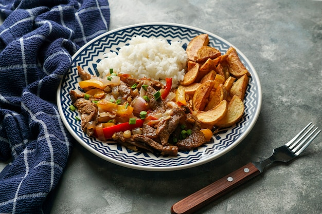 Peruvian dish lomo saltado, made of beef tenderloin with red onion, yellow chili, tomatoes, with potato fries and rice