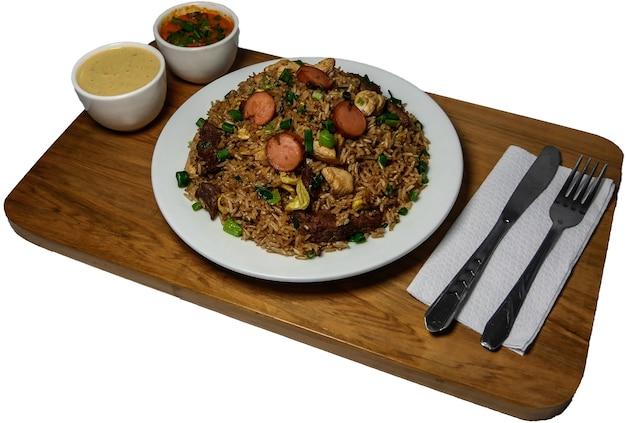 Перуанская еда арроз чауфа, тарелка жареного риса с овощами и разными видами мяса