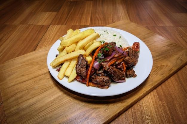페루 음식 lomo saltado, 고기, 양파, 노란 고추, 파슬리, 흰 쌀과 간장을 곁들인 감자 튀김, 칼 붙이 및 나무 배경이있는 흰색 접시에.