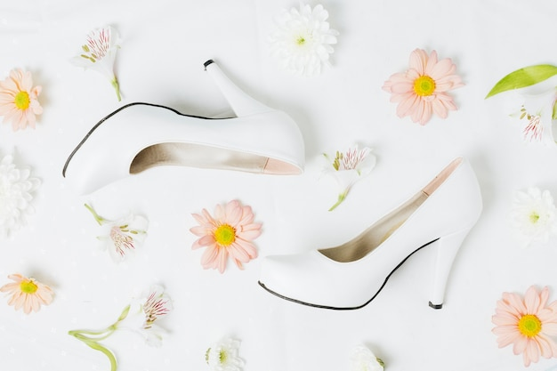 Peruvian lily and gerbera flowers with wedding high heels on white backdrop