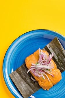 ペルーのタマレ、典型的なペルーの朝食。トウモロコシから作られ、チキンを詰めて、紫オニオンサラダを添えてください。