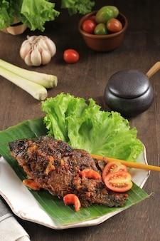 금붕어를 사용하는 pesmol 물고기. 팬에 튀긴 생선을 추가합니다. 달콤하고 신맛이 나는 인도네시아 서부 자바의 pesmol 일반적으로 생선 요리법