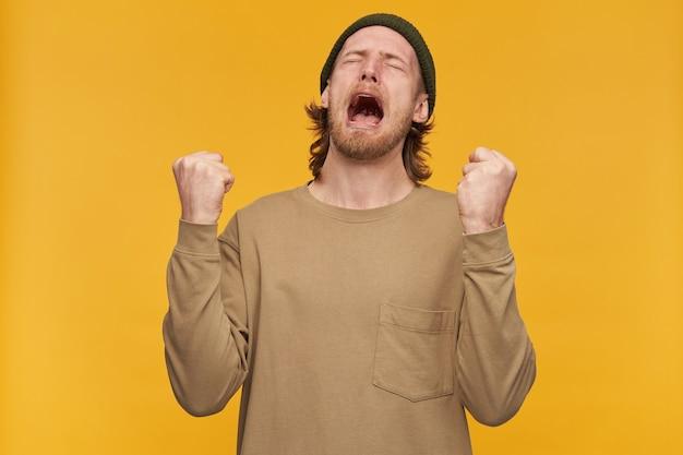 Pessimista maschio, ragazzo barbuto senza speranza con acconciatura bionda. indossare berretto verde e maglione beige. stringe i pugni e urla disperato. stare isolato su una parete gialla