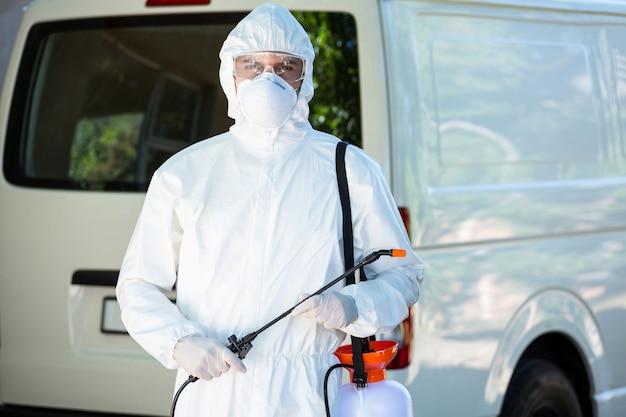 Pest control man standing behind a van