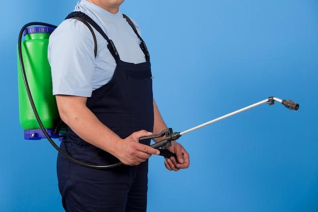 屋内で殺虫剤を均一に散布する害虫駆除作業員。