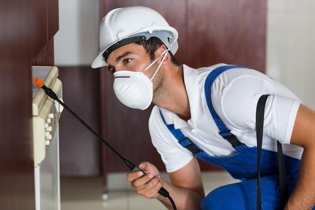 Pest worker using sprayer on cabinets in kitchen