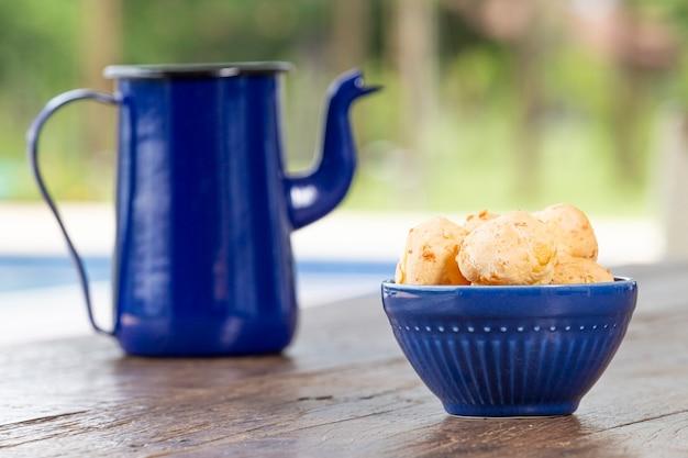 Pestic brazilian, 치즈 빵. 소박한 테이블에. 그리고 바닥은 파란색 커피 포트입니다.