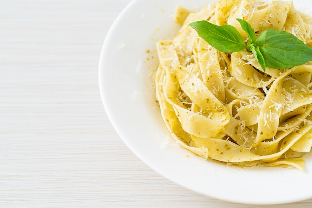 Pesto fettuccine pasta with parmesan cheese on top - italian food style