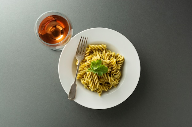 Pesto pasta and rose wine glass in white plate over gray background. italian food.
