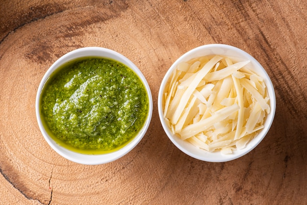 Pesto sauce in a bowl with the ingredients in the background. olive oil, garlic and basil.