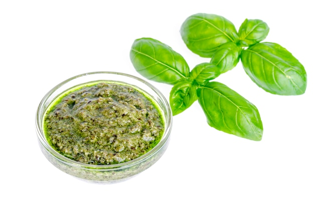 Pesto sauce and fresh green basil leaves.