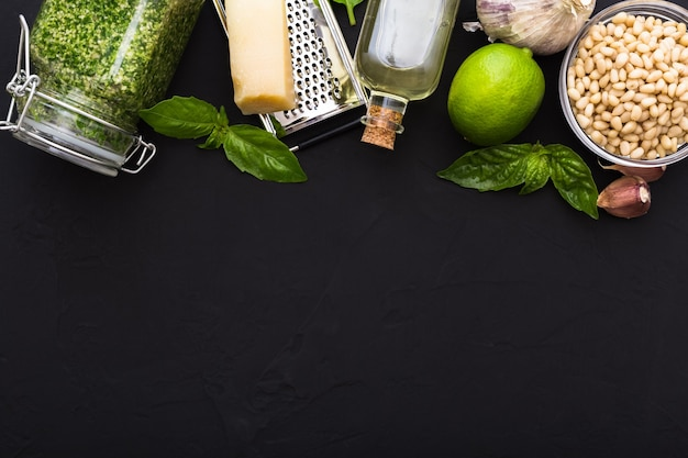 Pesto sauce in glass jar and ingredients for making pesto sauce. flat lay with copy space for text