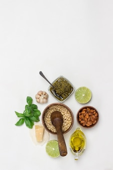 Pesto sauce and ingredients. pine nuts in wooden mortar, unpeeled pine nuts in bowl, olive oil, pesto bowl, basil leaves, parmesan, garlic, lemon. flat lay. white background. copy space