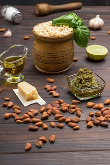 Pesto sauce and ingredients. unpeeled pine nuts, olive oil, pesto bowl, pine nuts in wooden mortar, basil leaves, parmesan, garlic, lemon. top view.  dark wood background