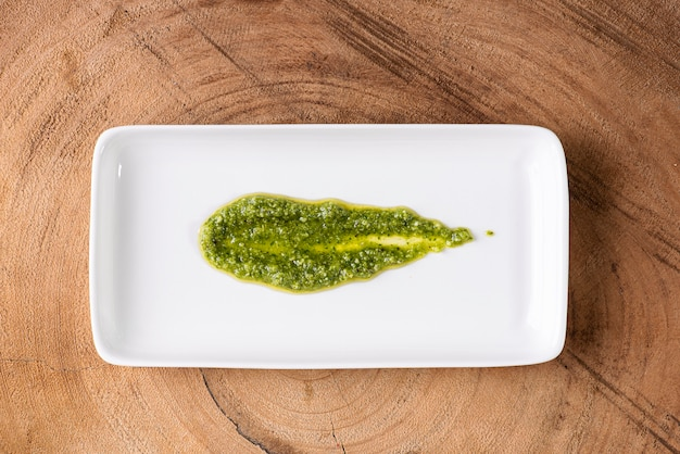 Pesto sauce. in a transparent glass with the ingredients in the surface. olive oil, garlic and basil.
