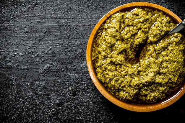 Pesto sauce in wooden bowl with spoon. on black rustic