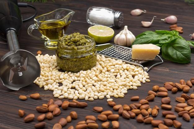 Песто. кедровые орехи неочищенные, соус песто в банке, пармезан на терке, чеснок, базилик, венчик, лимон. вид сверху. темный деревянный фон