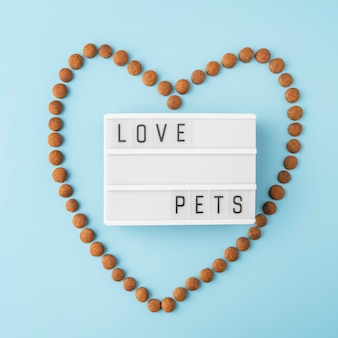 Pet accessories still life concept with dry food in heart shape