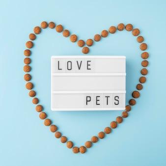 Концепция натюрморта аксессуаров для домашних животных с сухим кормом в форме сердца