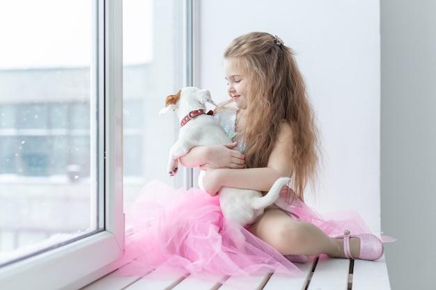 Концепция домашних животных и детей - ребенок с собакой джек рассел терьер дома.