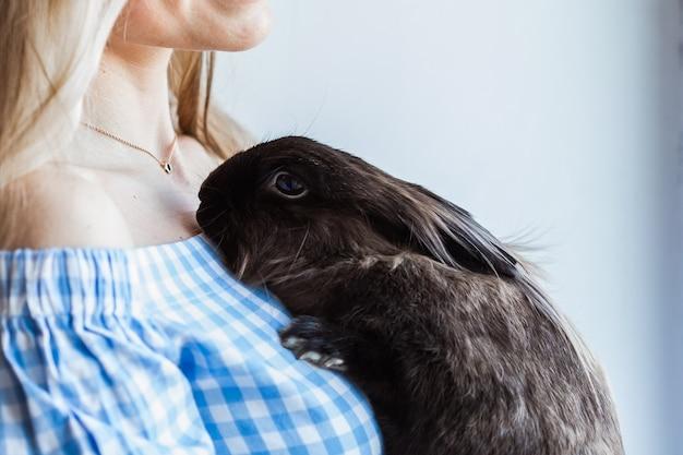 Домашнее животное и концепция пасхи - привлекательная девушка обнимает коричневого кролика дома, крупным планом.