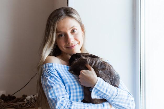 Домашнее животное и концепция пасхи - счастливая девушка обнимает коричневого кролика дома.
