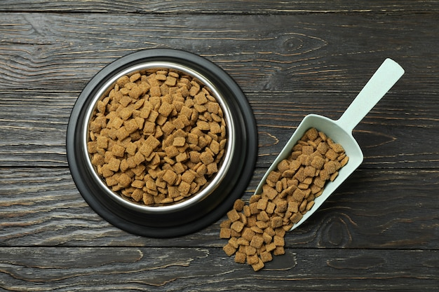 Pet bowl and scoop with feed on wooden